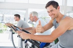 Portrait of happy man on exercise bike gesturing thumbs up at gym